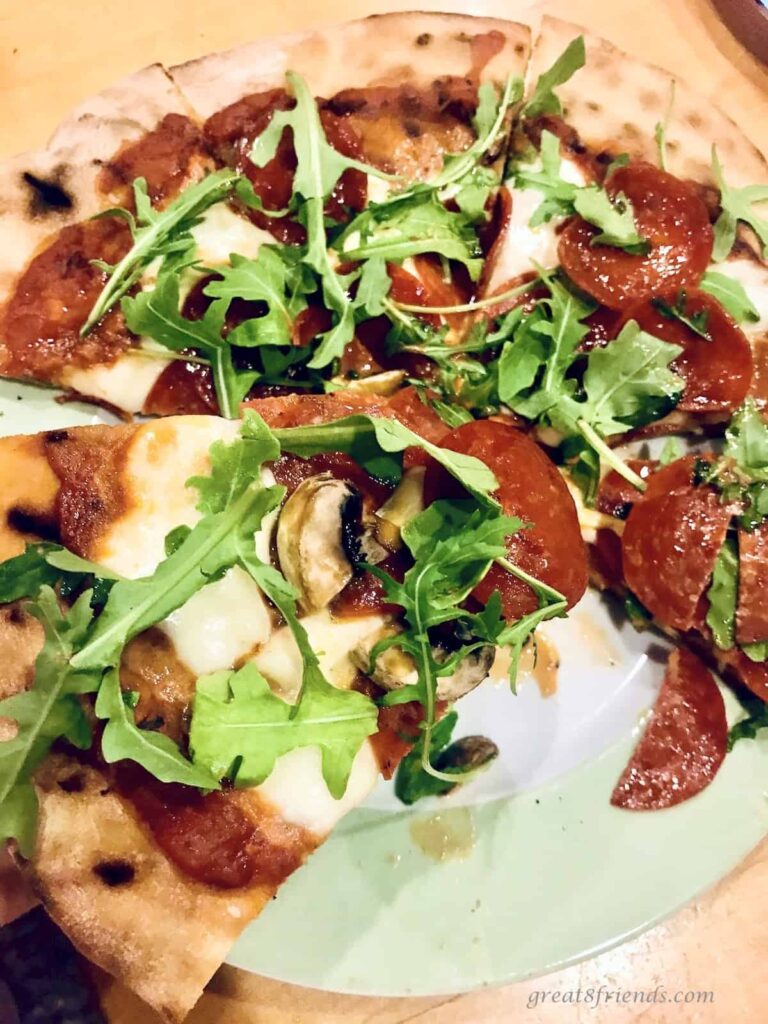 Unclose photo of a pizza cooked on the grill topped with sauce, cheese, pepperoni, and arugula.