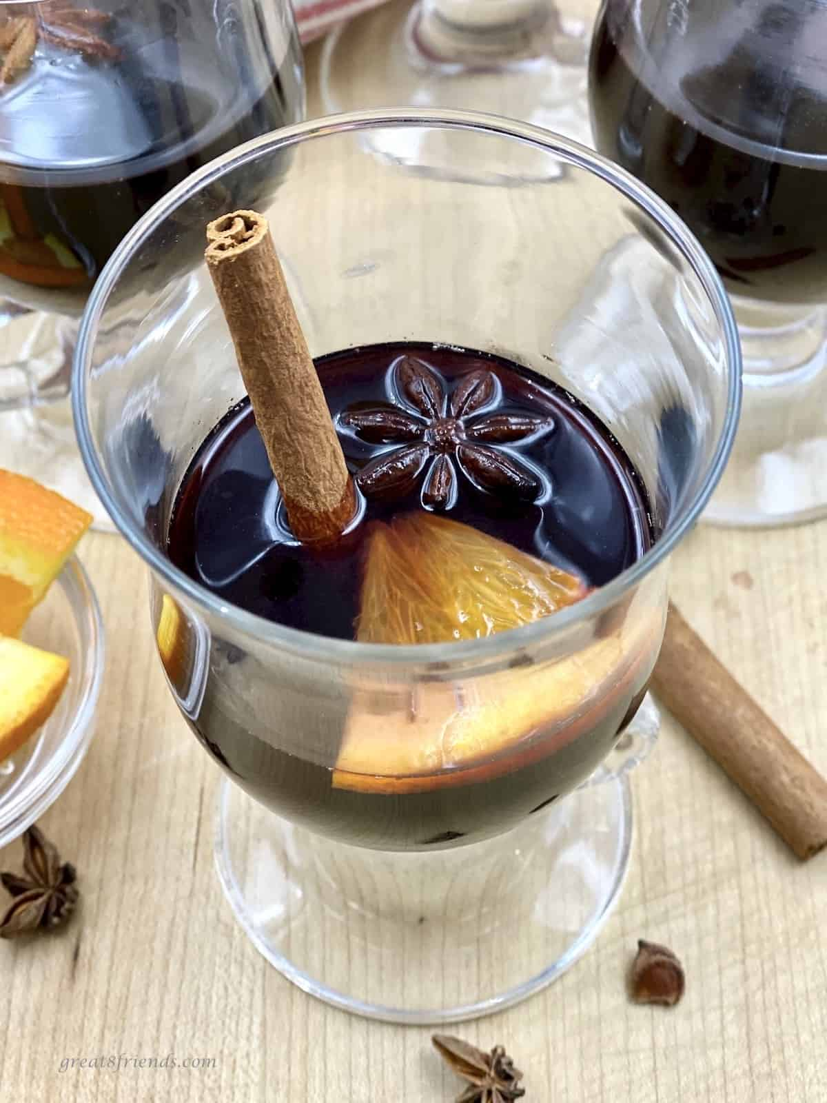 Glass cup with warm red wine garnished with a cinnamon stick, star anise and an orange slice.