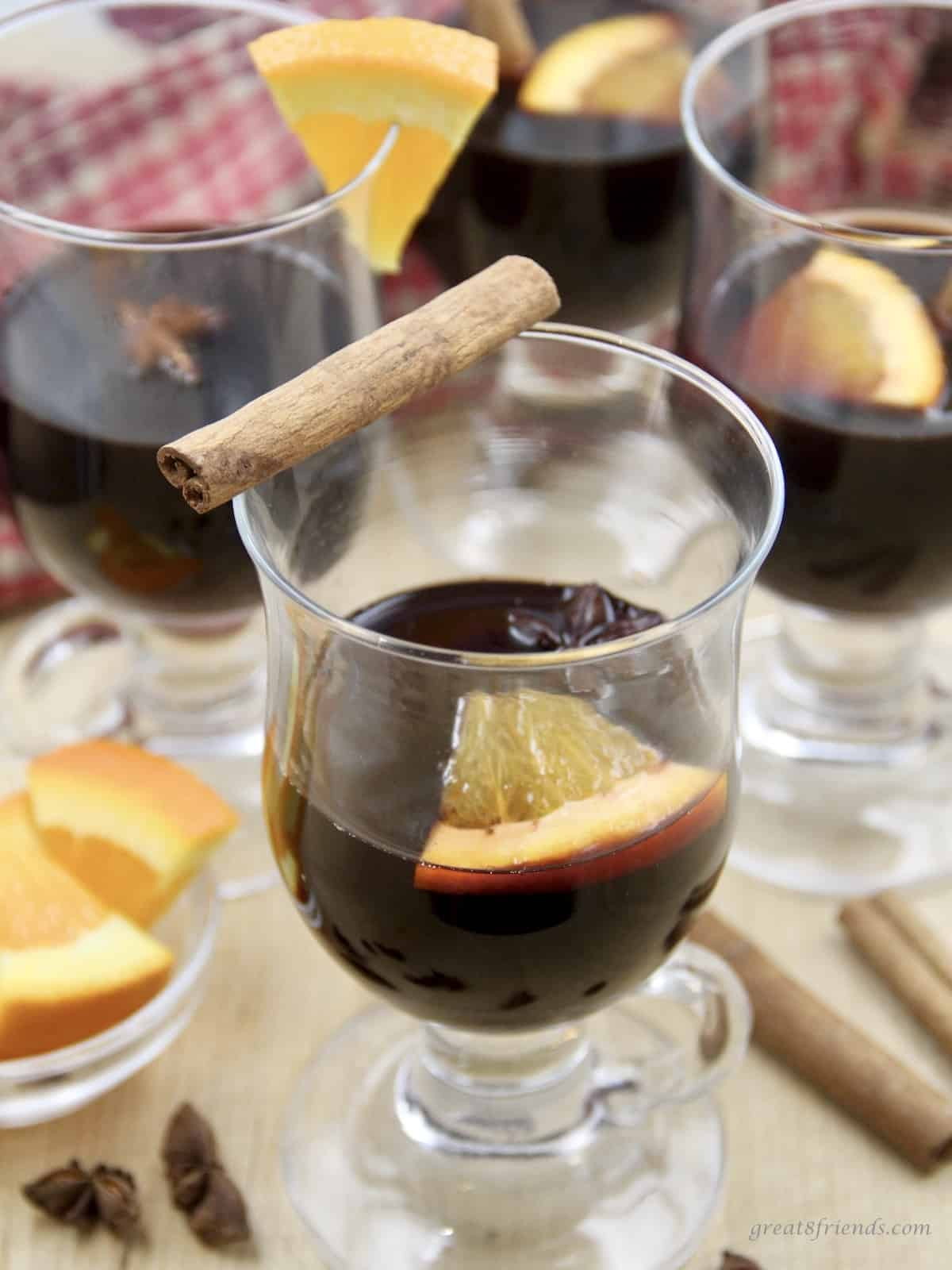 Mulled Red Wine served with a cinnamon stick and oranges.