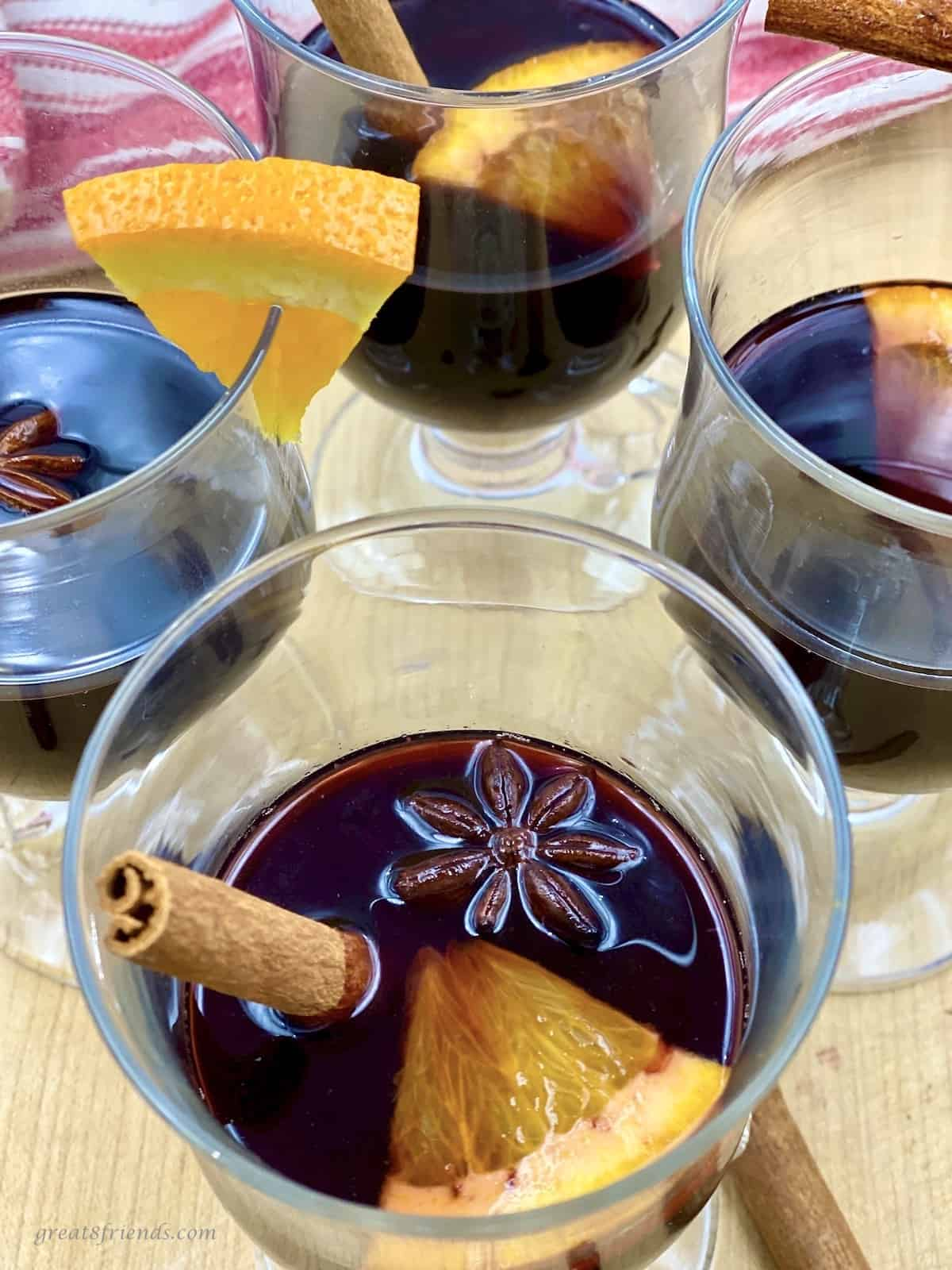 Four glass cups with mulled red wine garnished with cinnamon sticks and oranges slices.
