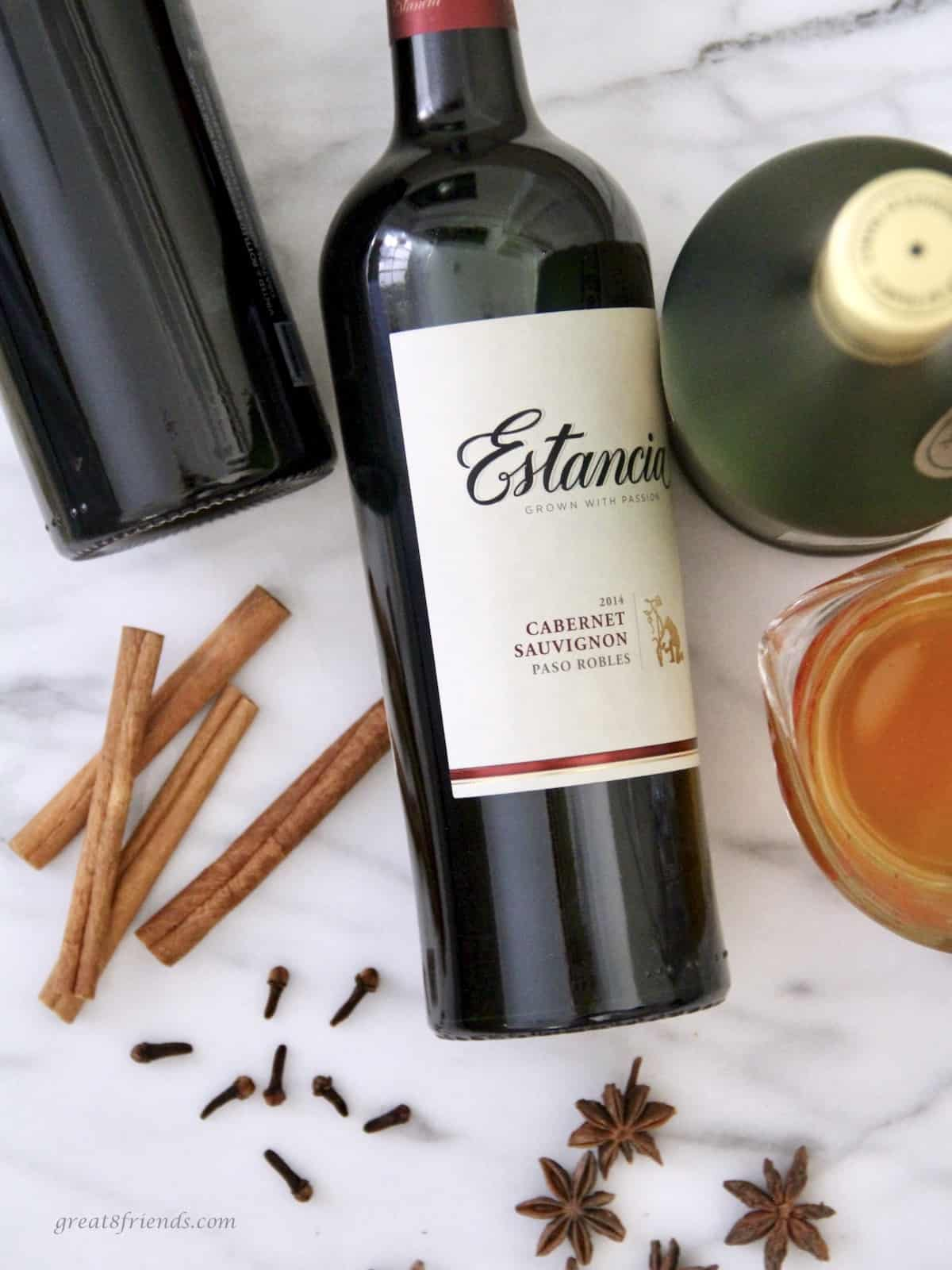 Two bottles of red wine, bottle of brandy, cup of honey, cinnamon sticks, whole cloves and anise stars all on a marble table.