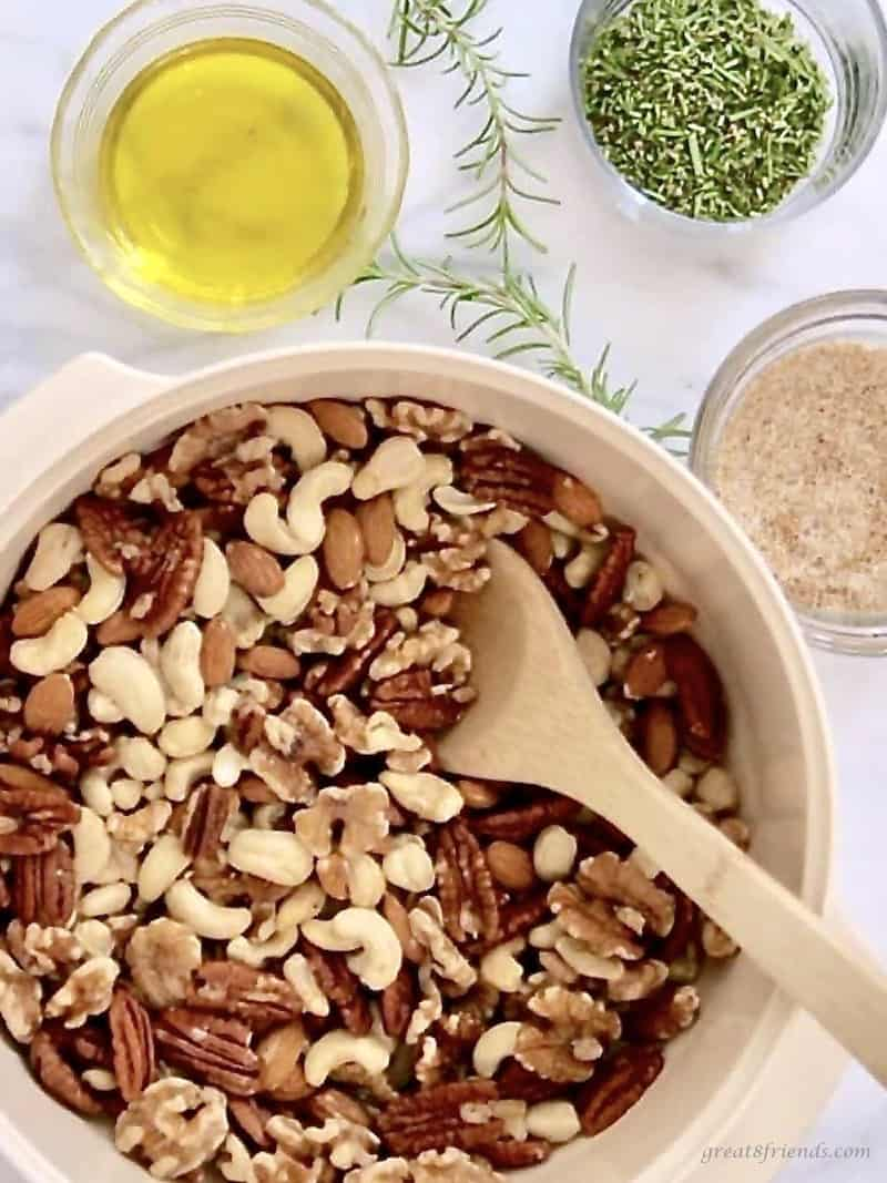 Mixed raw nuts in a bowl with rosemary and olive oil on the side.