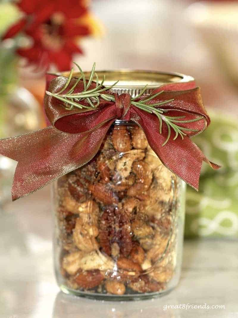 Rosemary spiced nuts in a mason jar with a red bow and rosemary sprig to decorate.