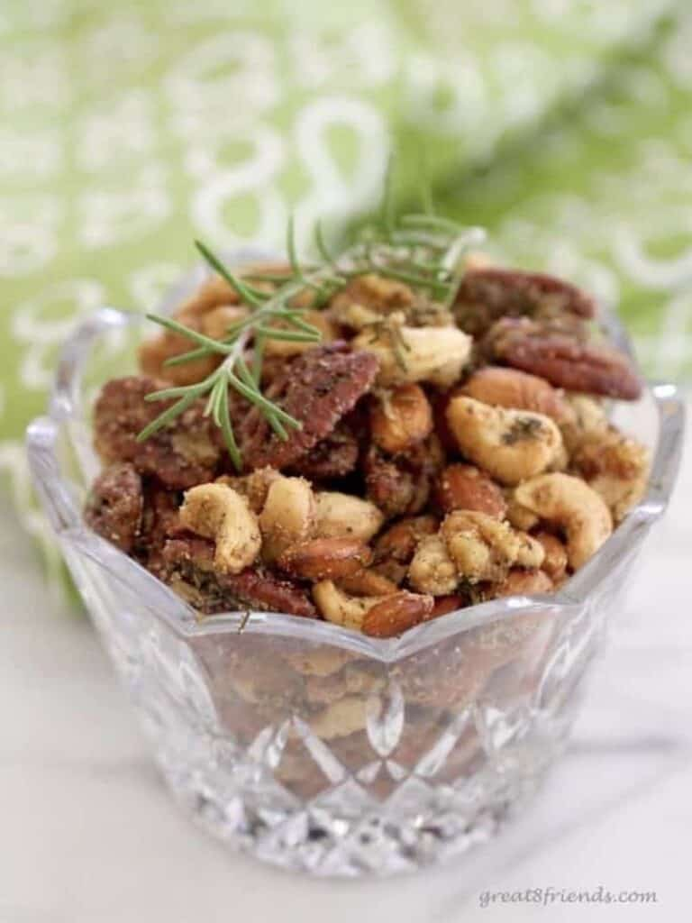 Rosemary spice nuts in a glass bowl.
