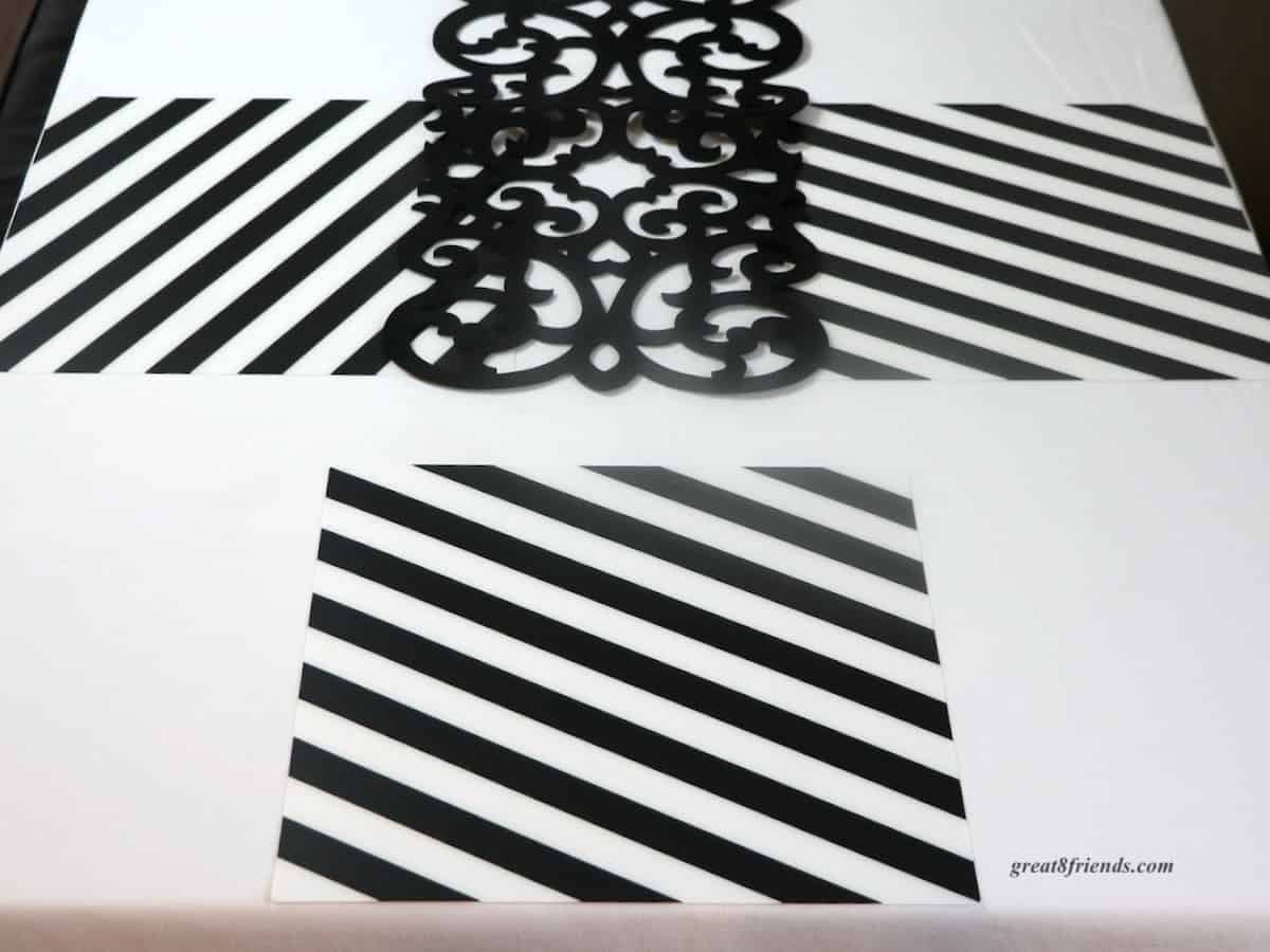 Black and white diagonal stripe placemats on white tablecloth.