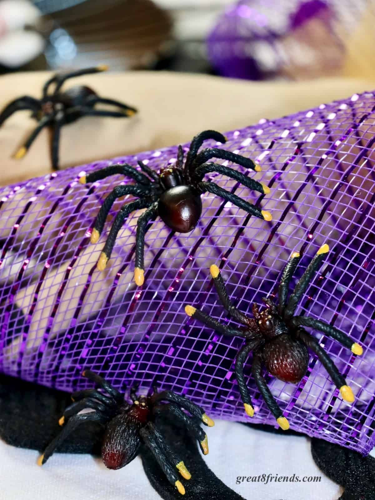 Black plastic spiders crawling on purple mesh.