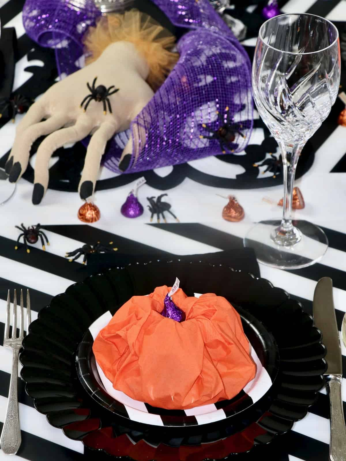 Halloween table setting with paper napkin pumpkin and creepy hand centerpiece.