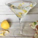 A martini with served with lemon peel as garnish in the glass.