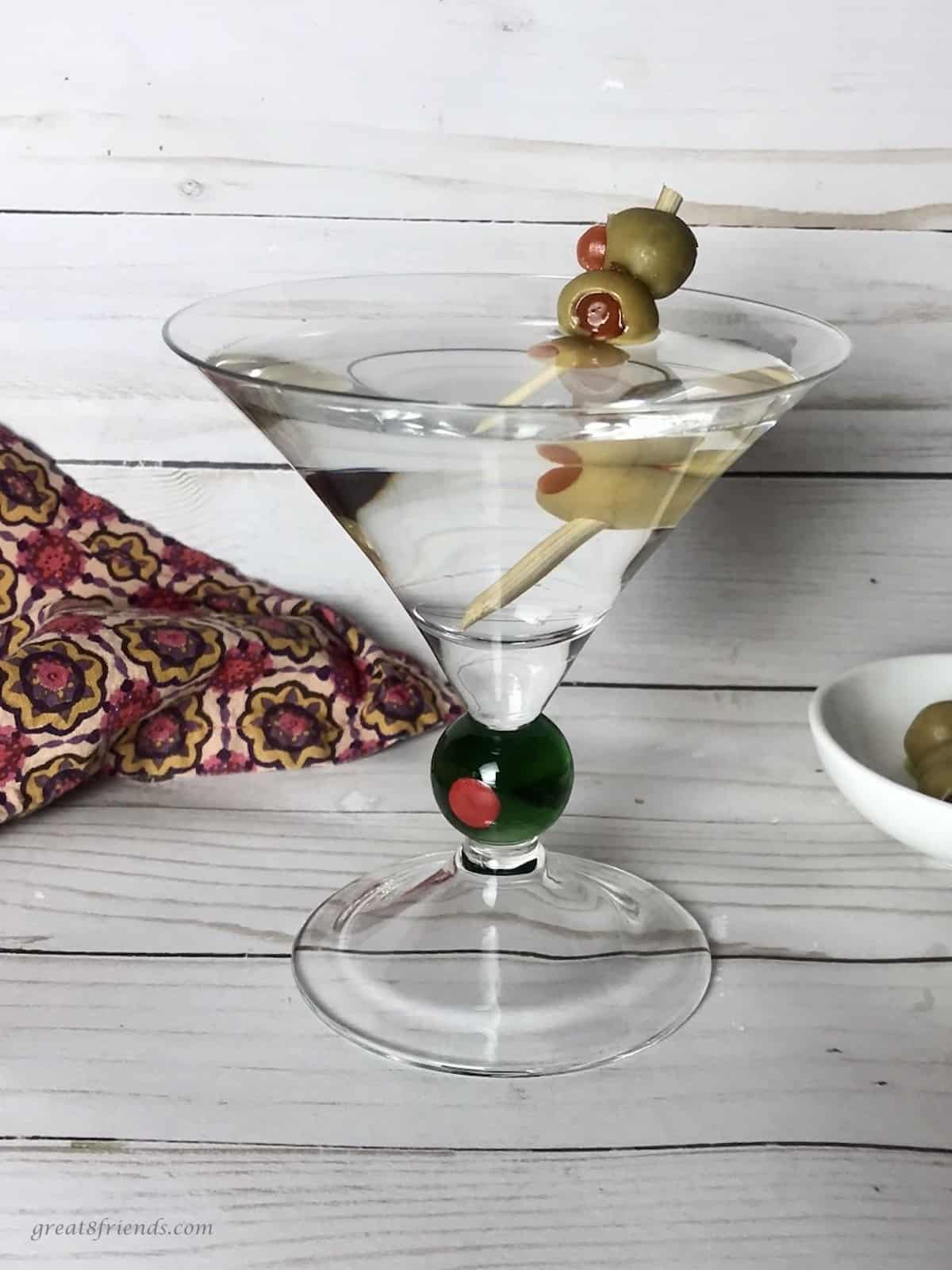 A classic gin martini with three olives on a pick.