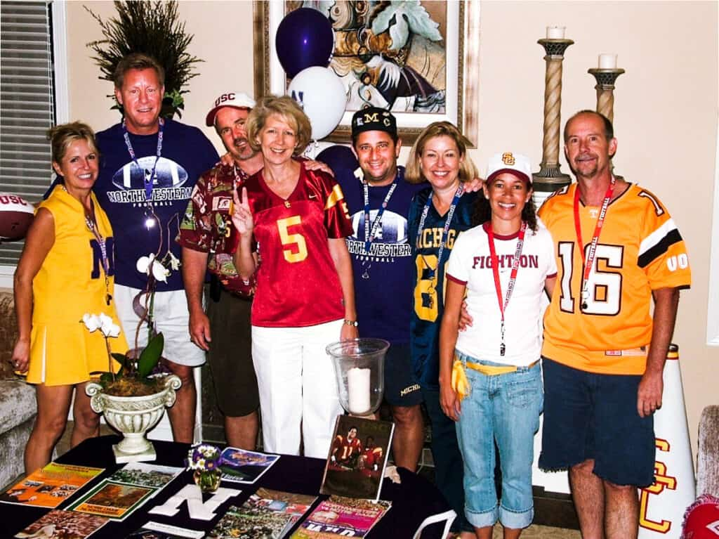 Four couples wearing college football team shirts.