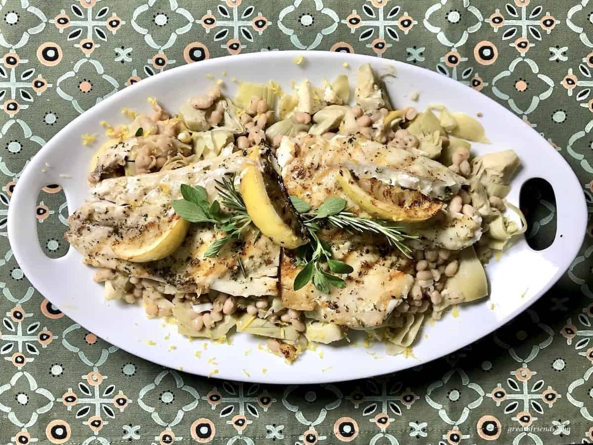 Sea bass with white beans and artichokes on an oval platter.