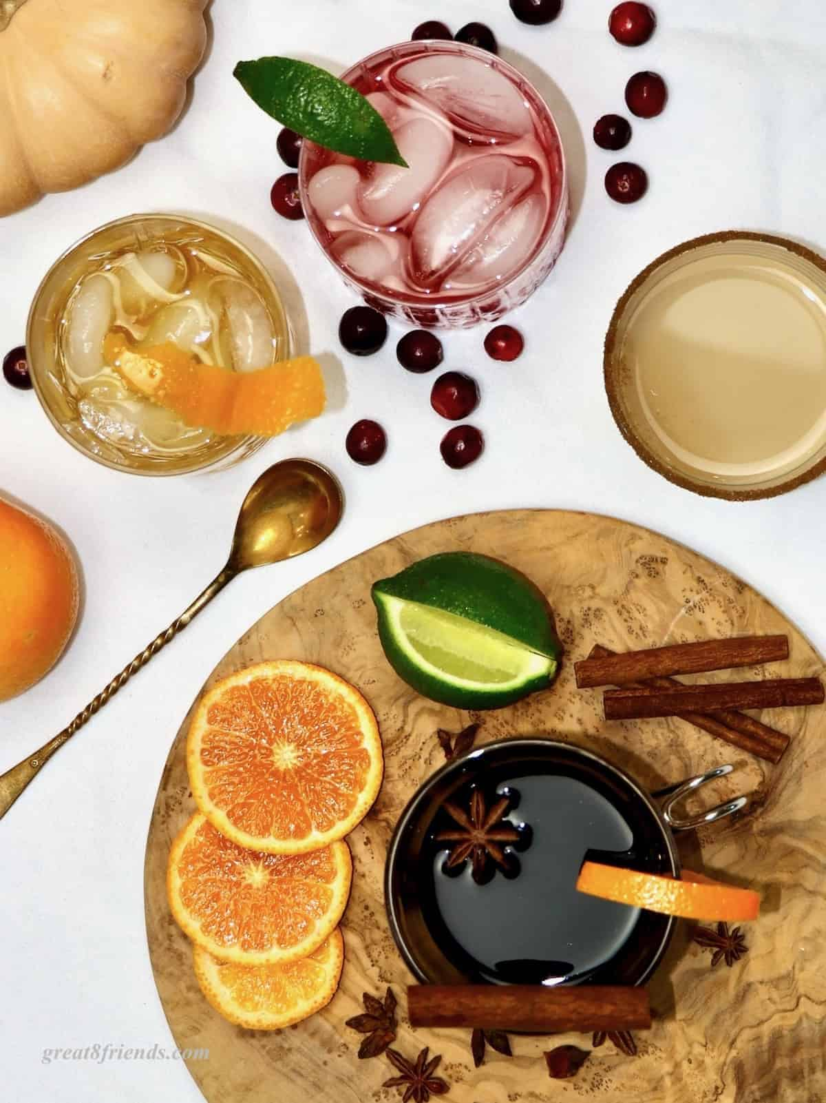 Overhead shot of a variety of fall cocktails with fruits and garnishes.
