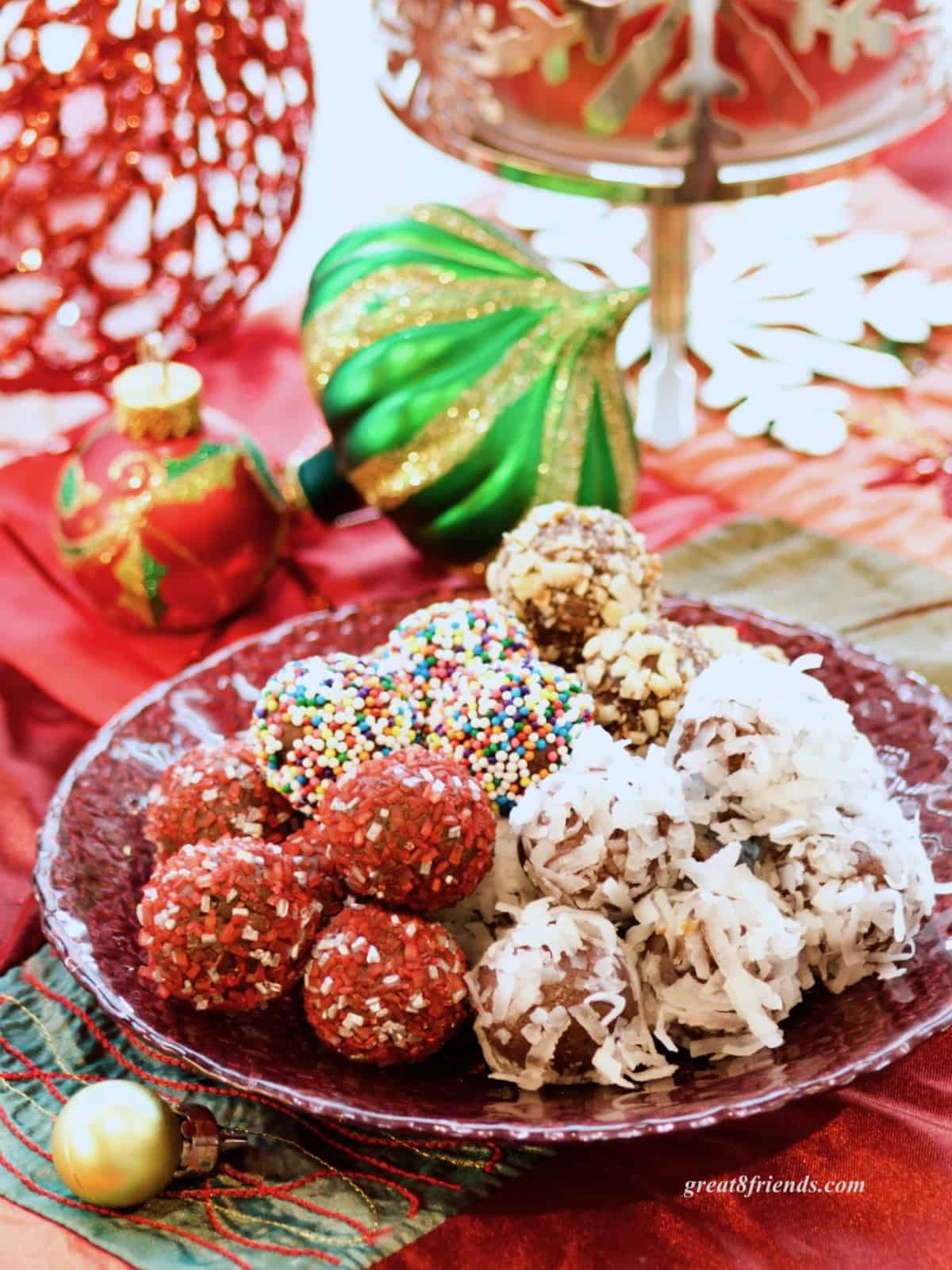 Chocolate truffles rolled in sprinkles and coconut on a Christmas table.