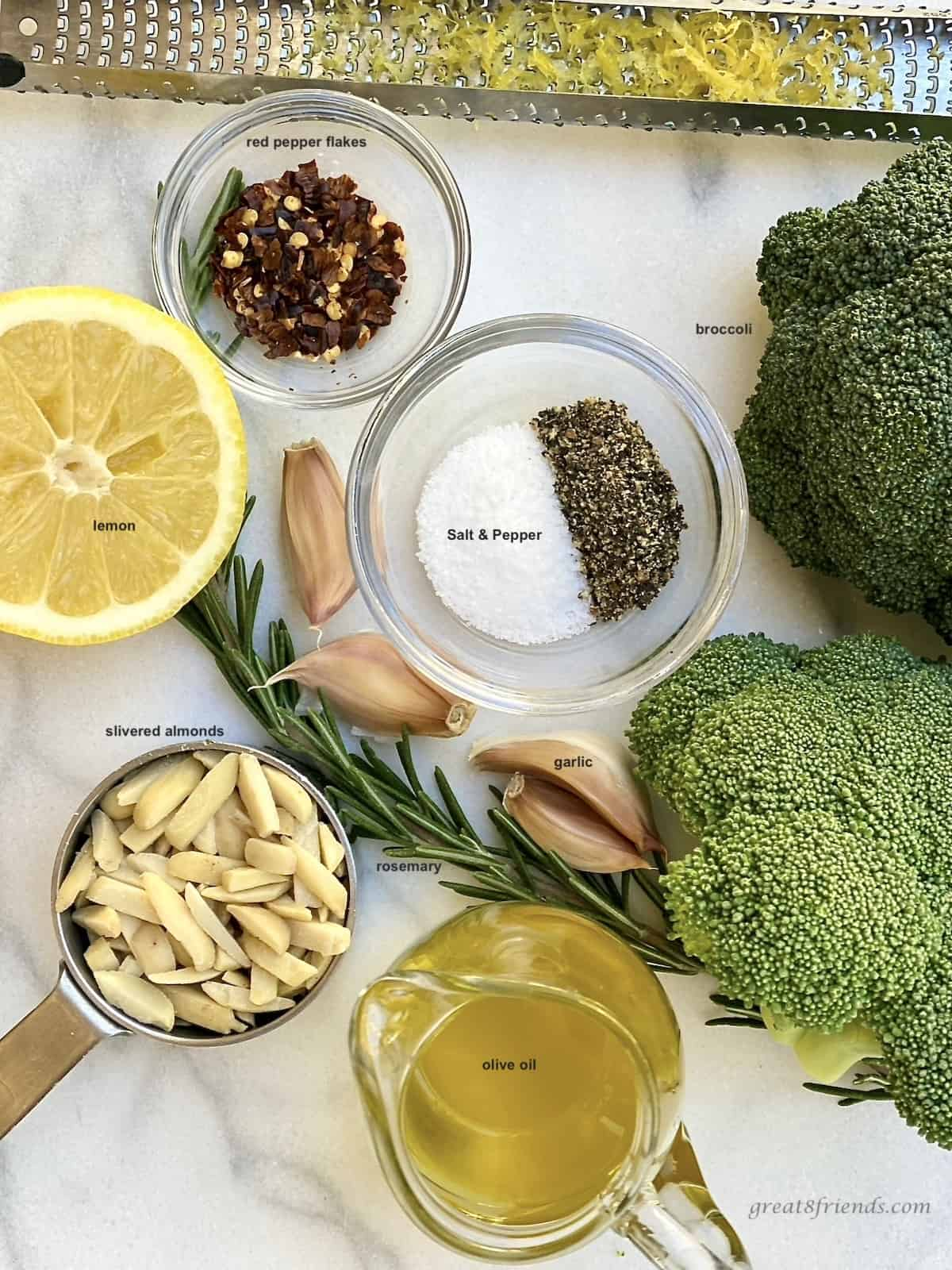 Ingredients for roasting broccoli. On the counter is broccoli, lemon, almonds, salt and pepper, olive oil, rosemary, garlic and red pepper flakes.