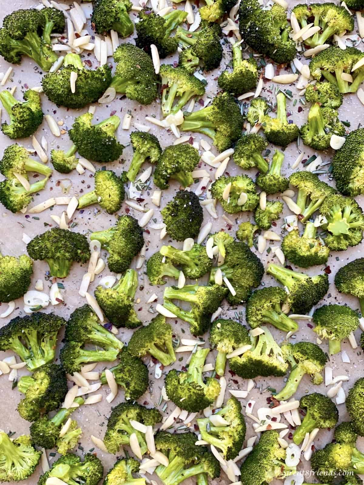 Broccoli florets on a baking sheet sprinkled with almonds and spices.