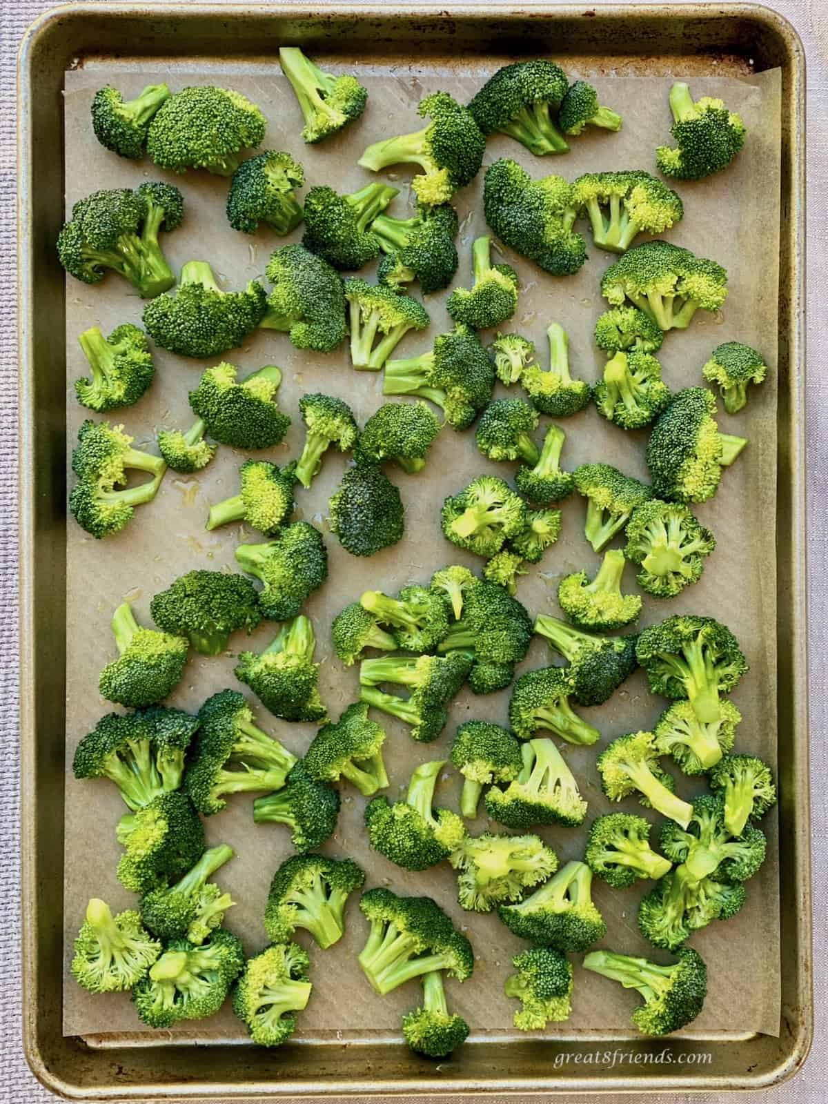 Raw broccoli florets on a baking sheet ready to be roasted in the oven.