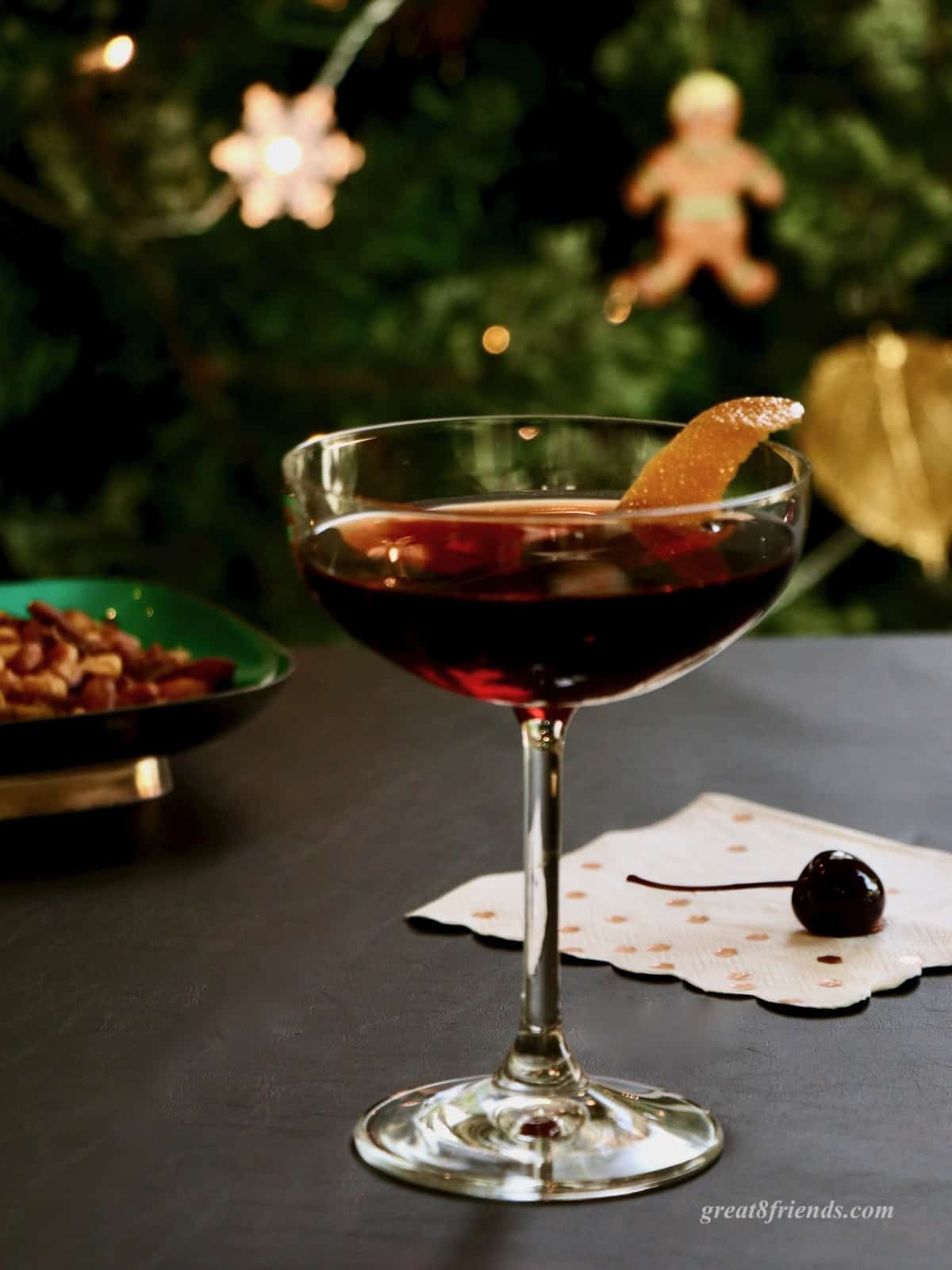 A cherry Manhattan in a coupe glass garnished with orange peel with a cherry on the table and nuts in background.