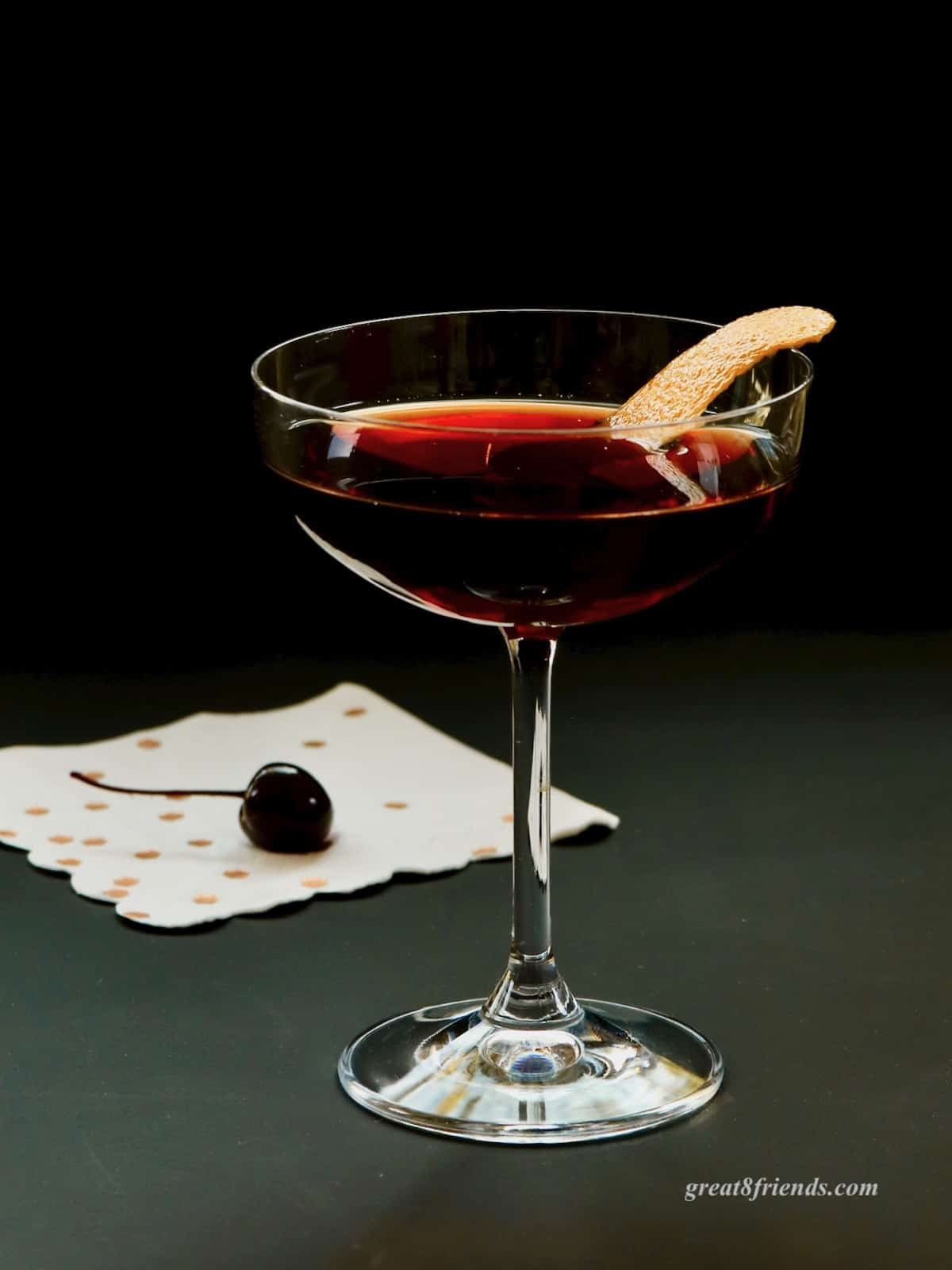 A cherry Manhattan in a coupe glass garnished with orange peel with a cherry on a napkin.