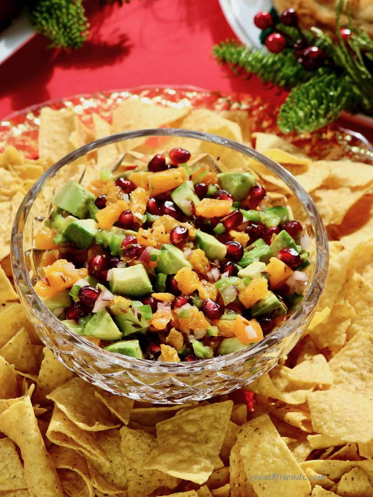 Pomegranate Avocado salsa in a crystal bowl surrounded by tortilla chips.