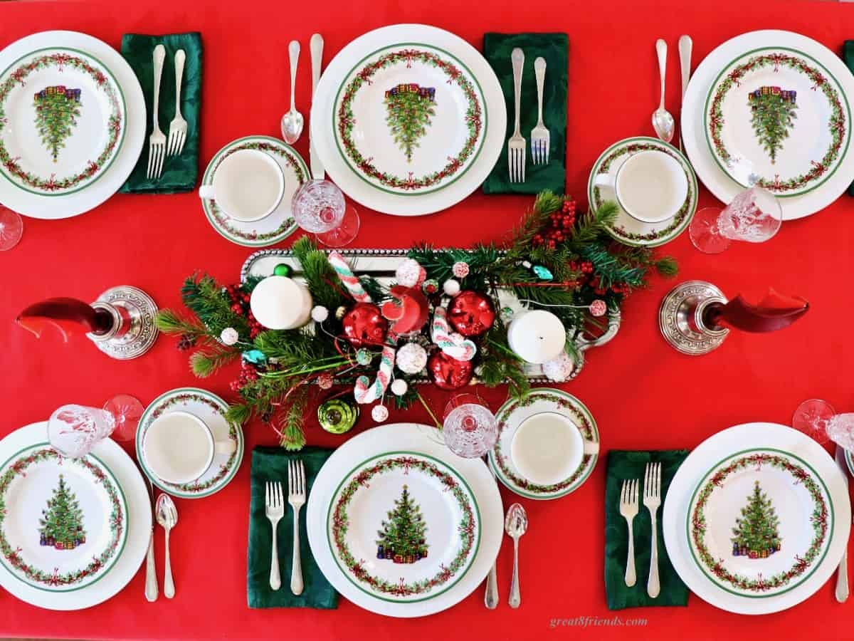 Overhead shot of table set for 6 with Christmas plates and Christmas centerpiece.