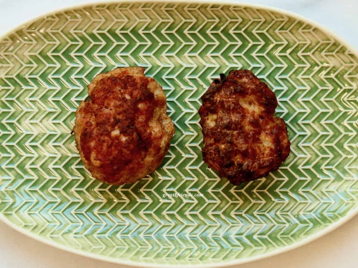 Overhead shot of 2 Danish meatballs side by side on a green oval plate.