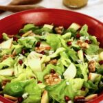 Close up of salad in a red wooden bowl.