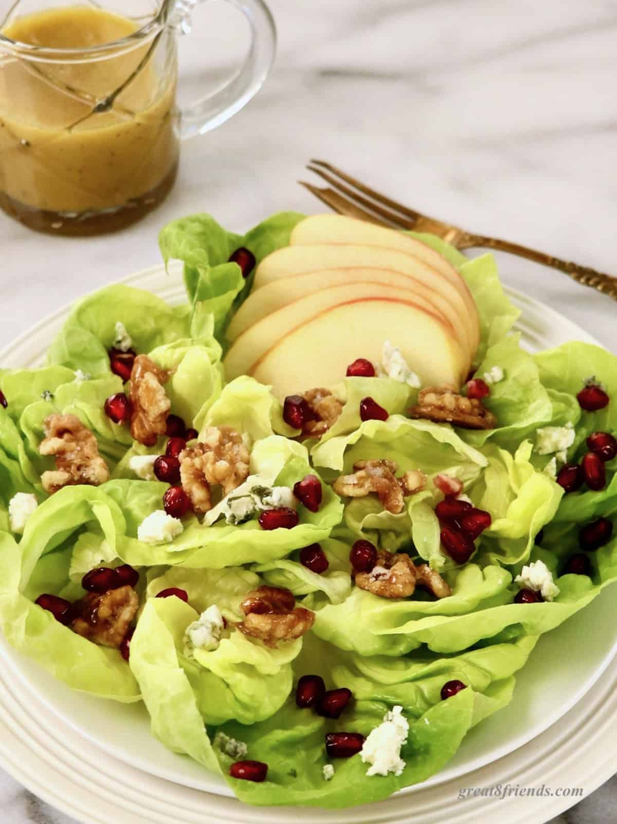 Salad with walnuts, bleu cheese and sliced apples with dressing in the background.