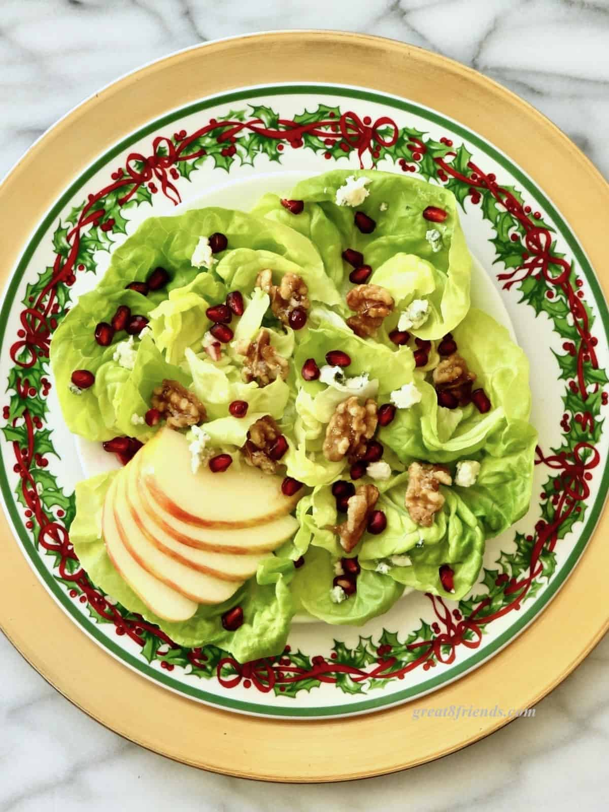Overhead shot of Christmas plate with a pomegranate, apple and walnut salad.