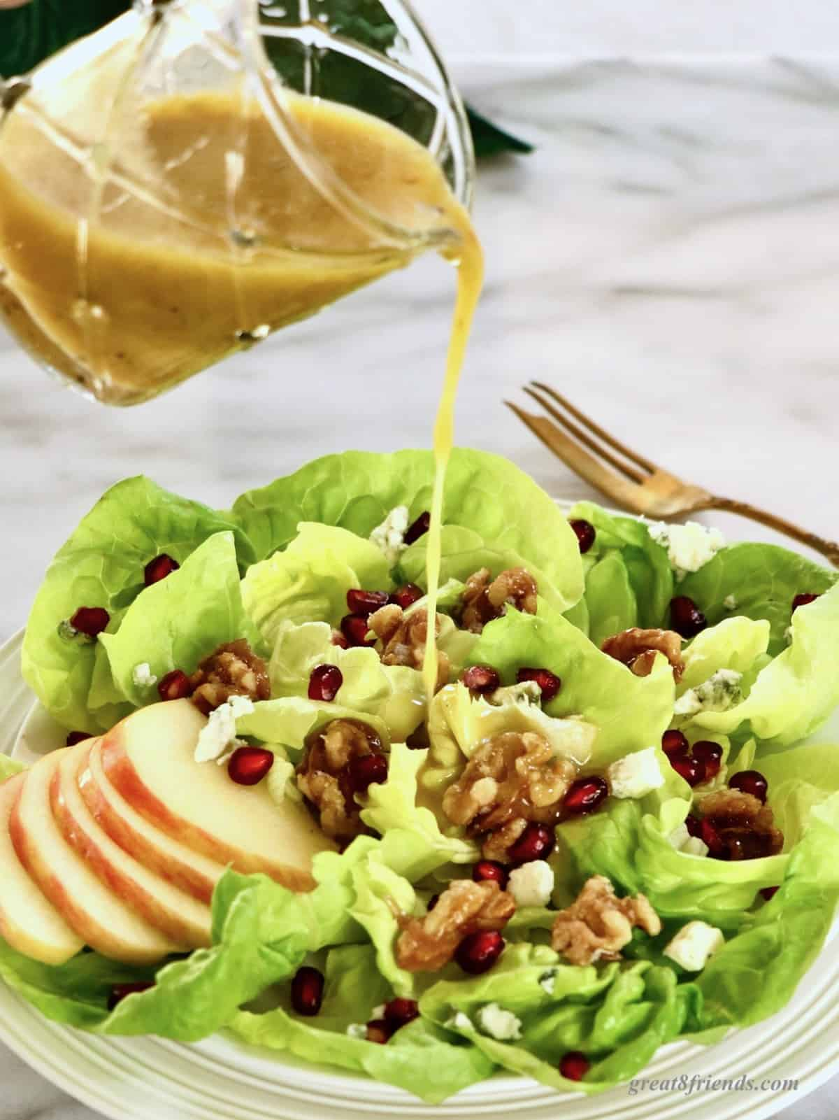Dressing being poured on salad with walnuts, sliced apples, and pomegranate seed.