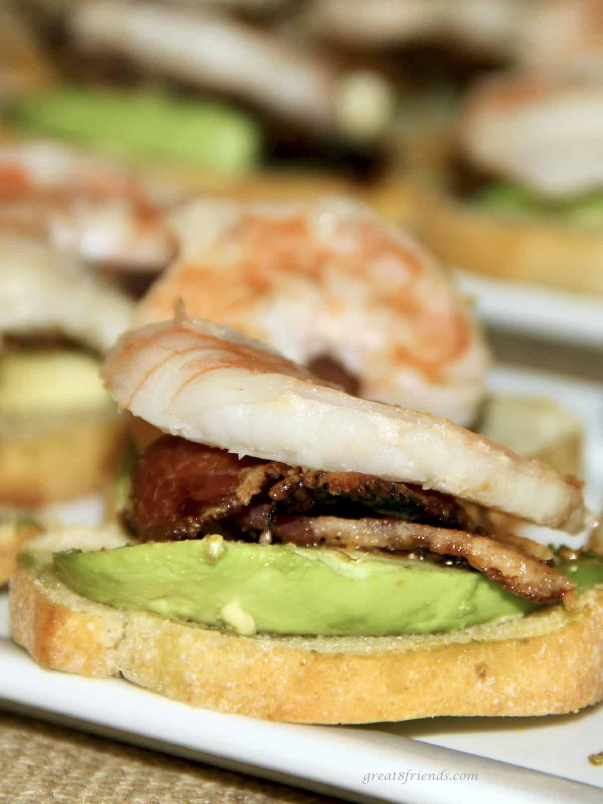 Unclose shot of a toasted piece of French bread with avocado, bacon and shrimp on top.