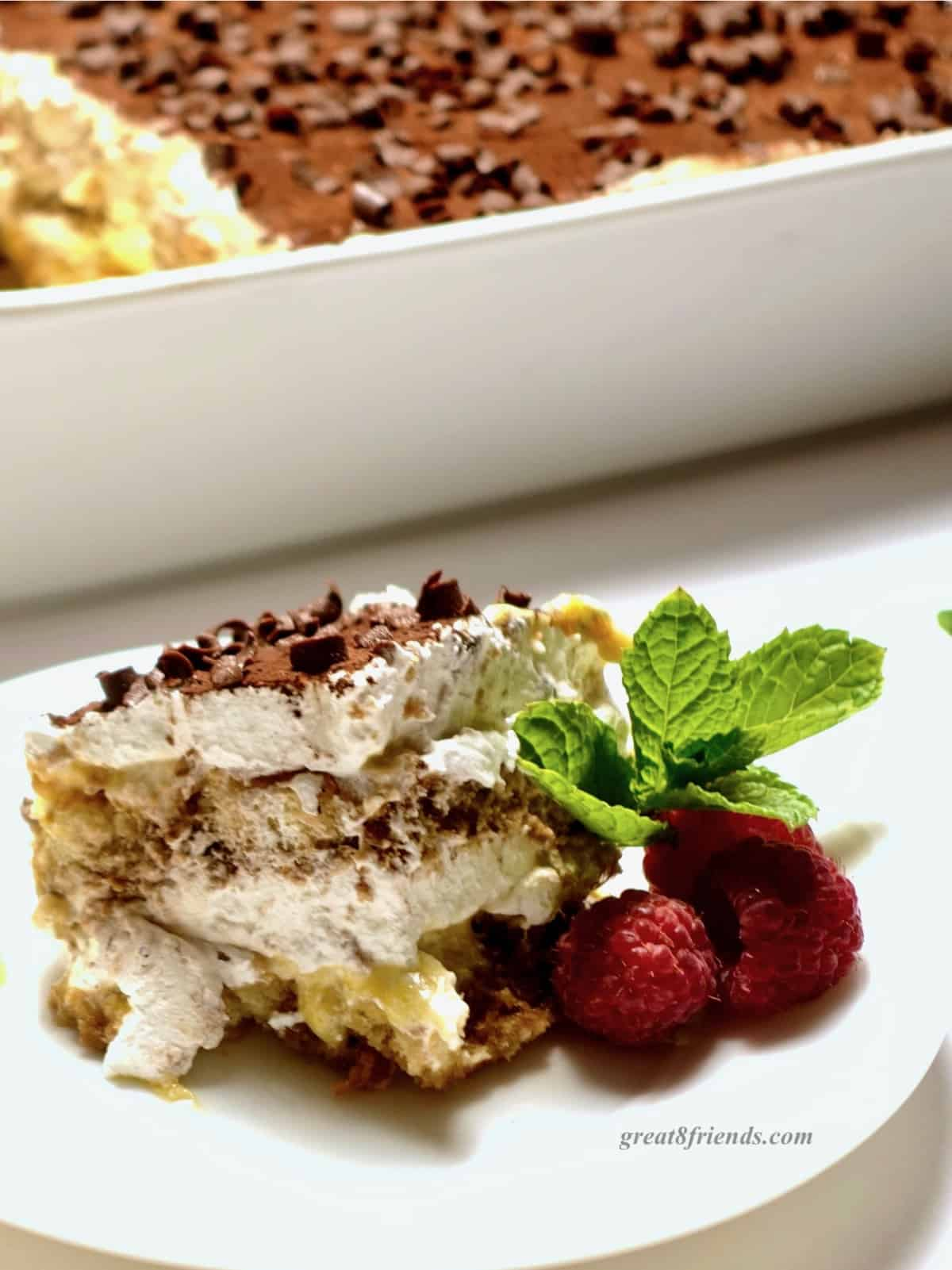 A piece of tiramisu on a plate garnished with raspberries and mint sprigs.