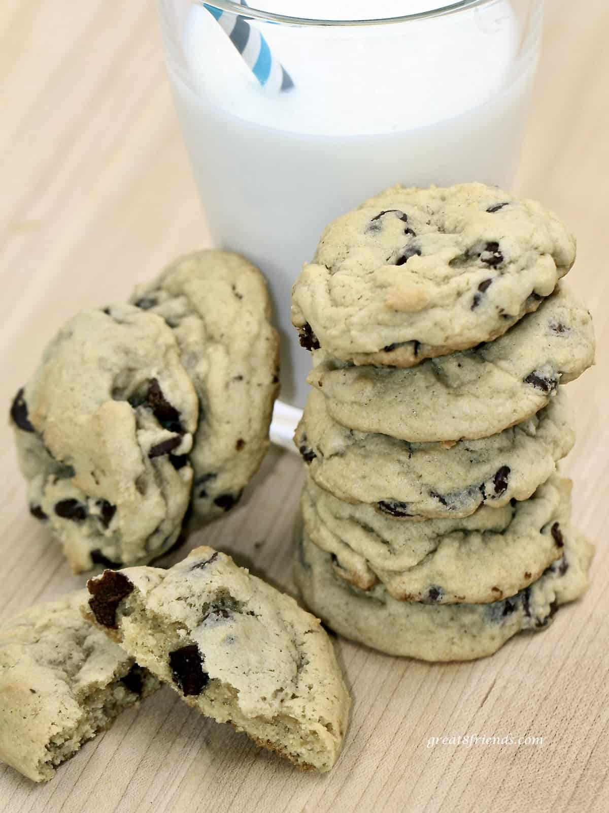 Chocolate chip cookies stacked on each other in front of a glass of milk.