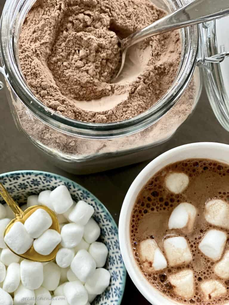 Overhead view of powdered cocoa mix, a cup of hot cocoa with marshmallow on top, and a bowl of mini marshmallows.