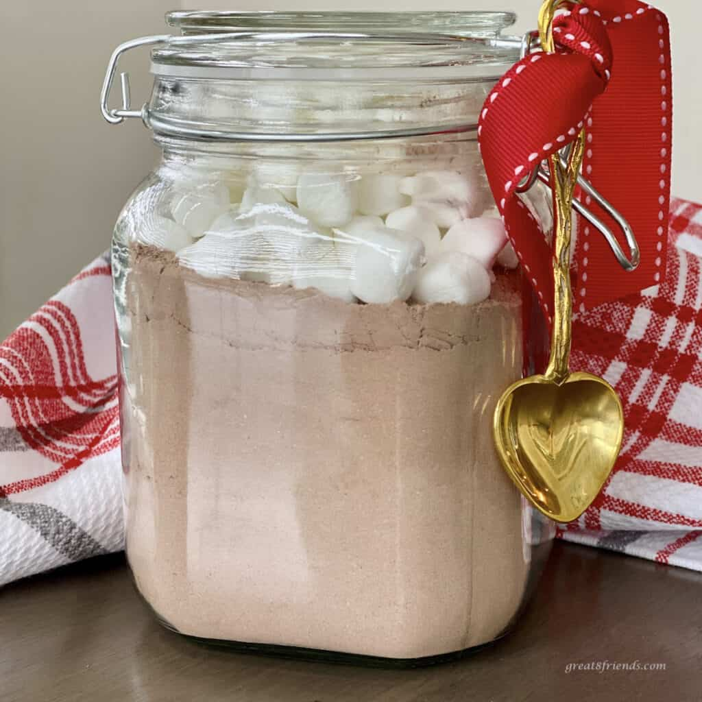 Hot cocoa mix in a jar with marshmallow on top wrapped as a gift with a red bow with a gold spoon hanging on the side.