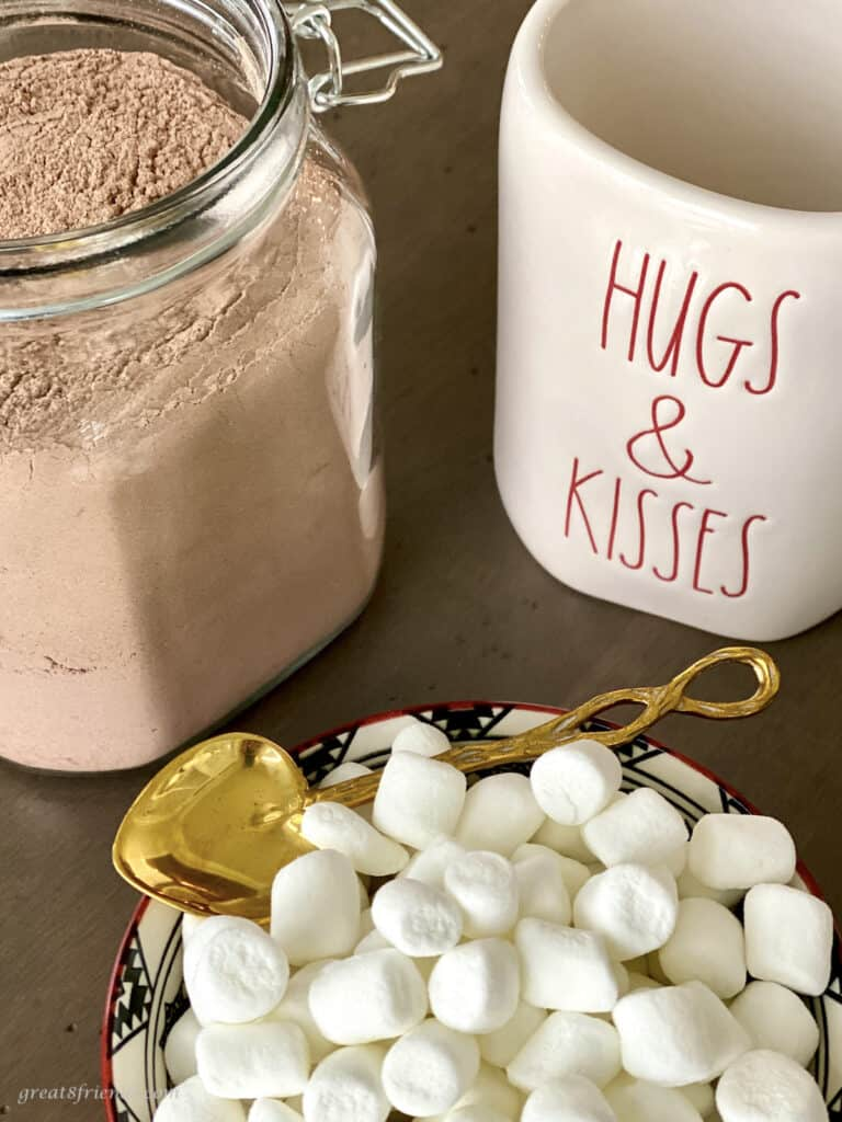 """A jar of homemade cocoa mix next to a mug saying """"hugs & kisses"""" and a bowl of mini marshmallows with a gold colored spoon."""