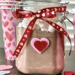 Powdered cocoa mix in a mason like jar with a ribbon tied around it and heart paper cups in the background.