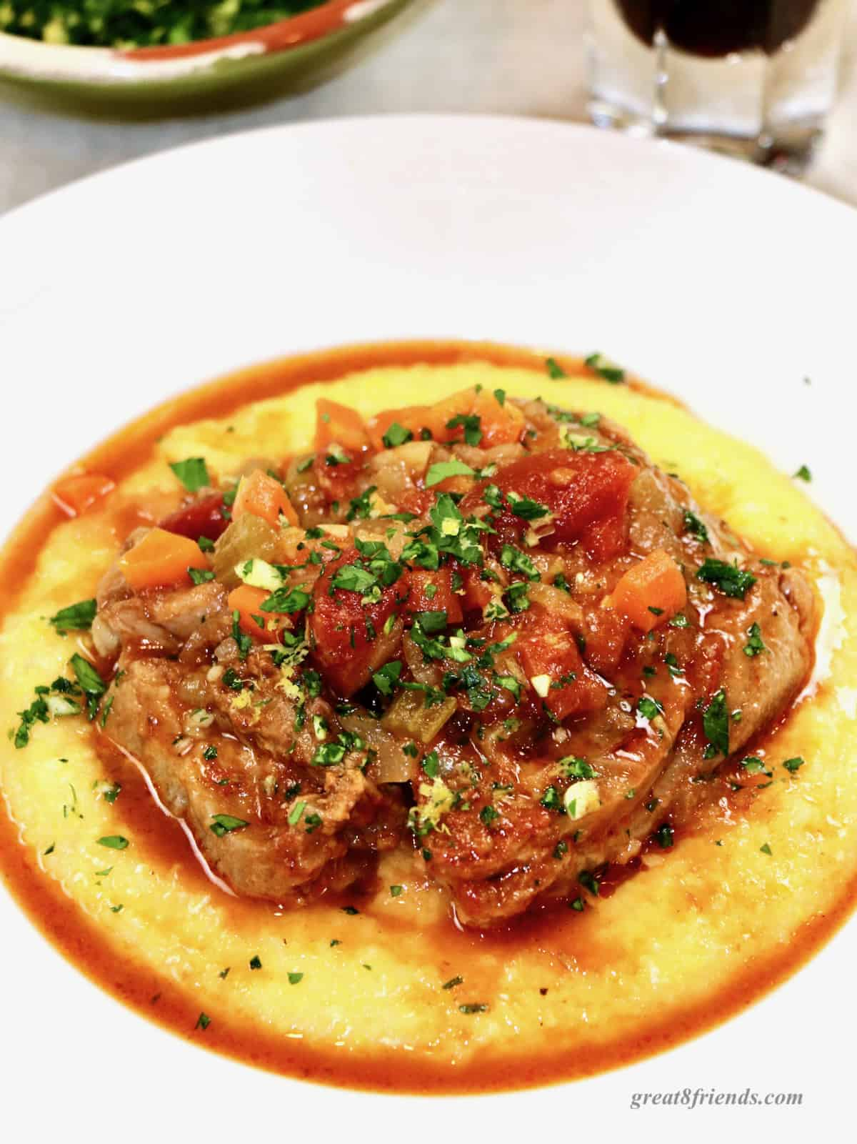 Osso buco on a bed of polenta in a white dish topped with gremolata.