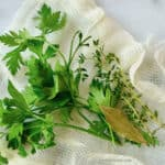 Sprigs of parsley and thyme with a bay leaf on top of a piece of cheesecloth.