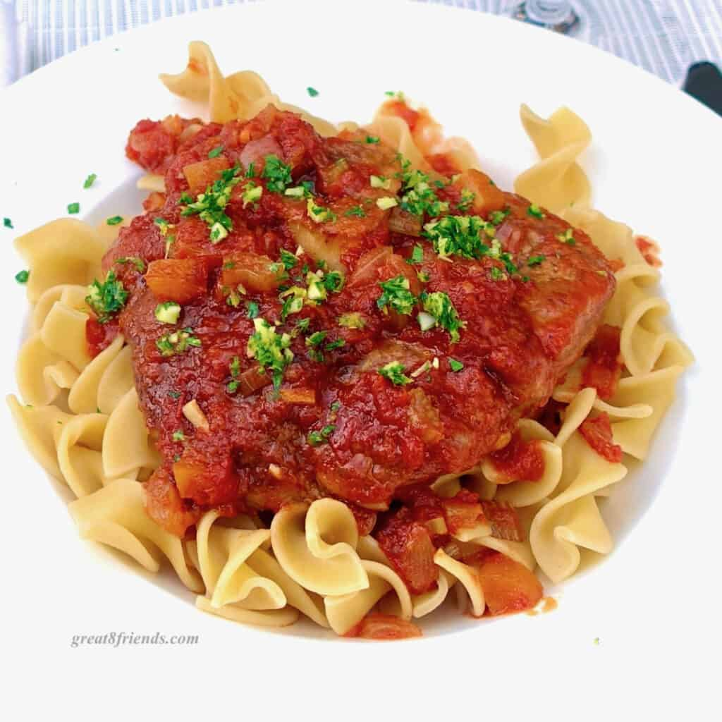 Osso buco on a bed of noodles in a white dish topped with gremolata.
