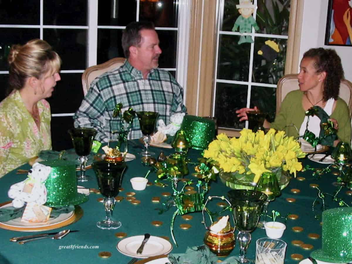 A man and two women sitting at a St. Patrick's Day decorated round table.