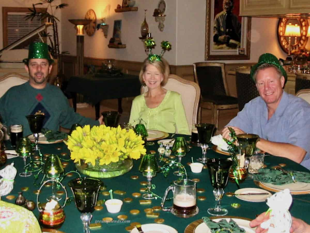 A woman and two men sitting at a St. Patrick's Day decorated round table.