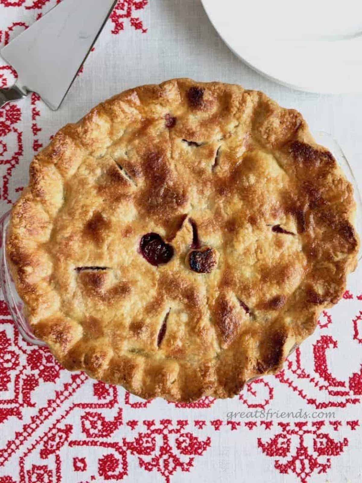 An overhead shot of a whole cherry pie on a red and white tablecloth.