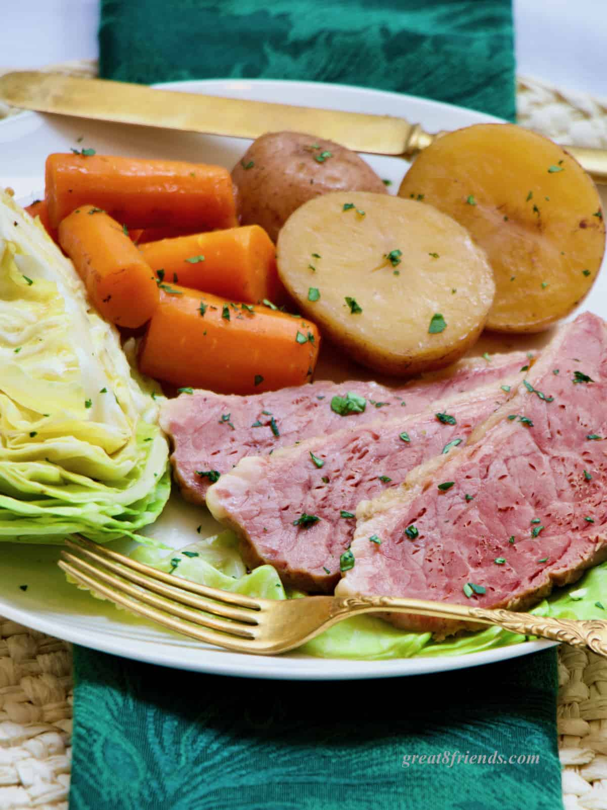 Three slices of corned beef, with a wedge of cabbage, some carrots and potatoes on a plate.