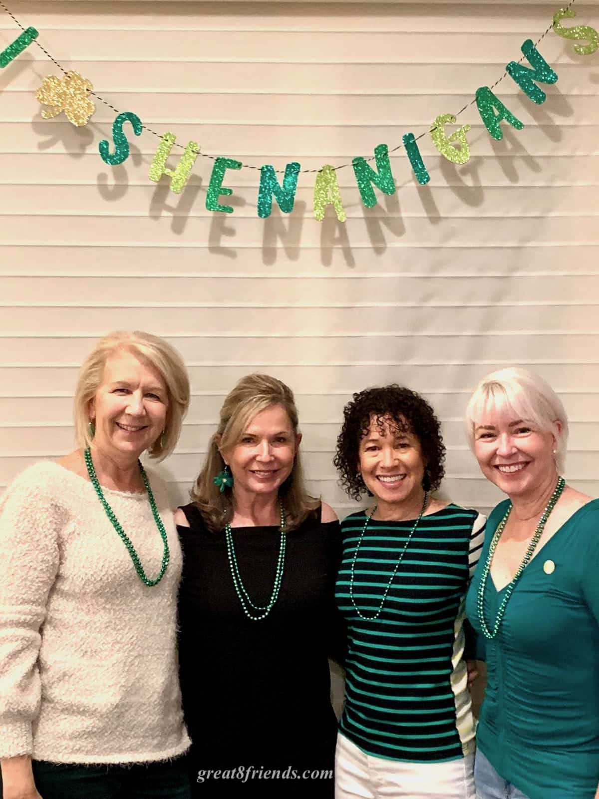 "Four ladies standing together under a glittery green sign that says, ""I love shenanigans."""