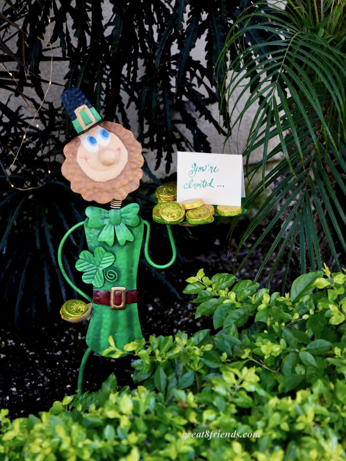 Metal garden leprechaun holding a small tray with gold foil chocolate coins and an invitation.