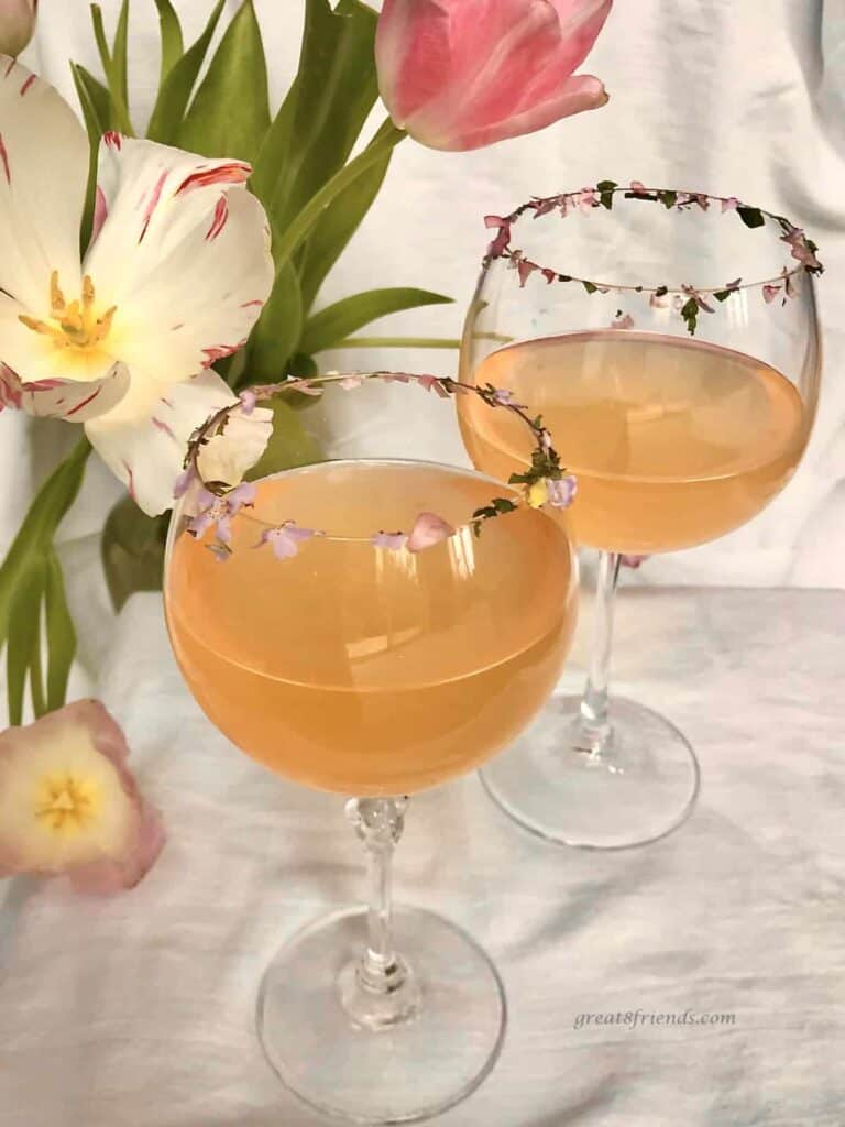 Two glasses of pink lemonade with edible flower bits on the rim of the glasses and a tulip flower on the table for decoration.