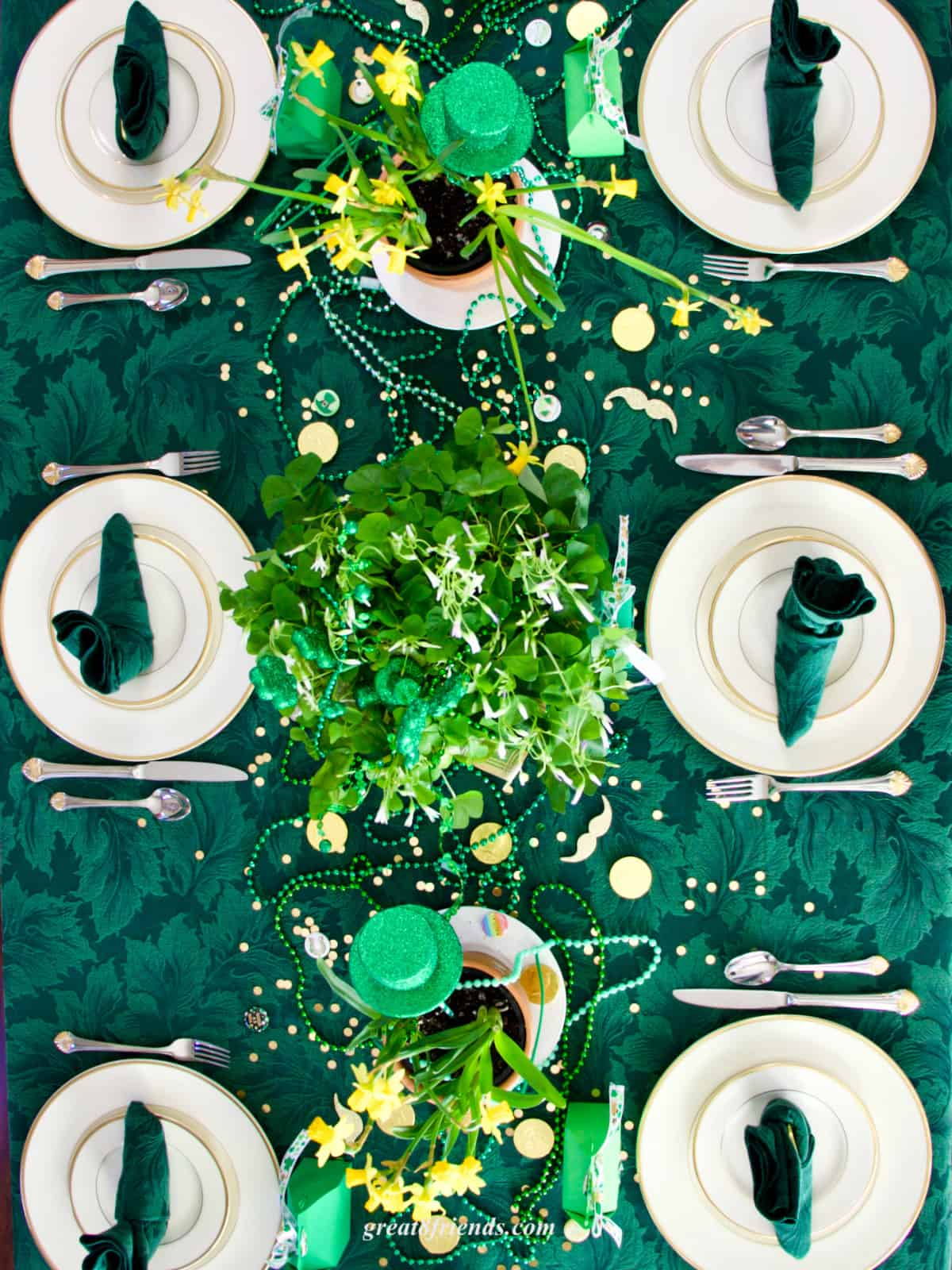Overhead shot of table set for St. Patrick's Day. With a shamrock centerpieces, gold rimmed china and green tablecloth and napkins.