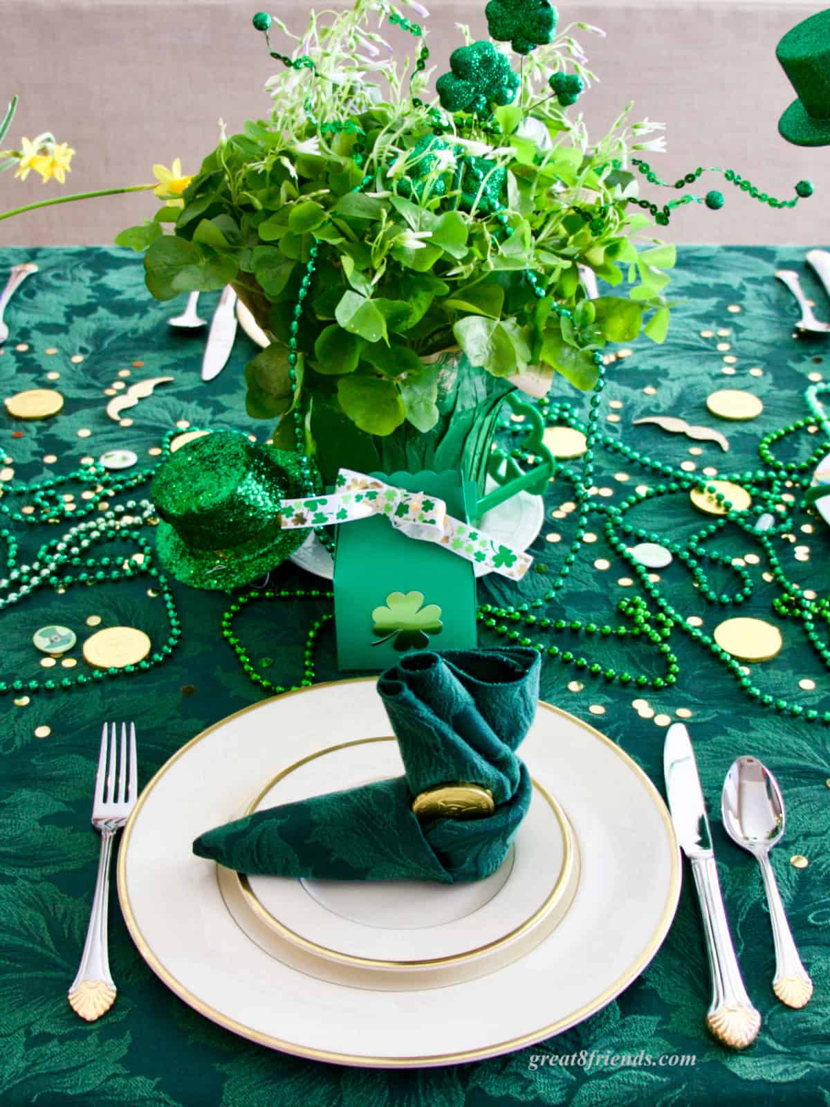 A St. Patrick's Day place setting with gold rimmed dishes, a shamrock centerpiece and the napkin folded in the shape of a leprechaun boot.