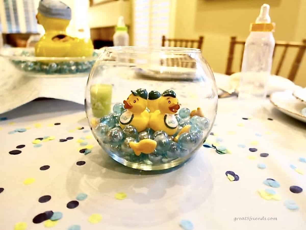 On a decorated table with confetti a glass fish bowl with blue glass marbles and rubber ducks inside.