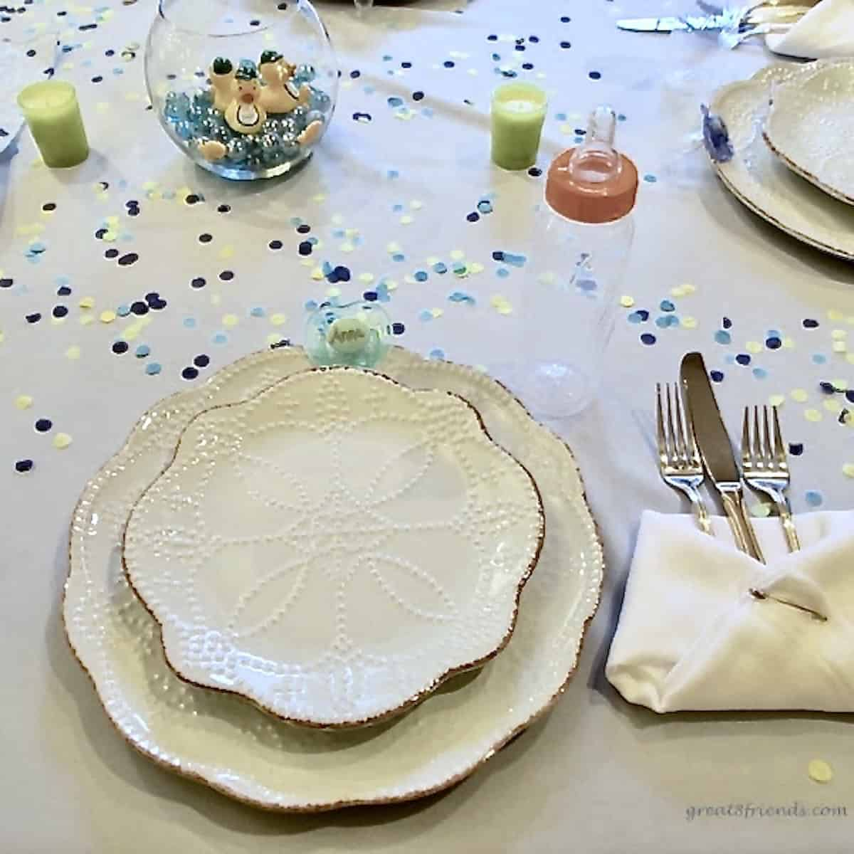 Table setting with confetti on a white table cloth, a baby bottle and a fish bowl with glass marbles and small rubber ducks.